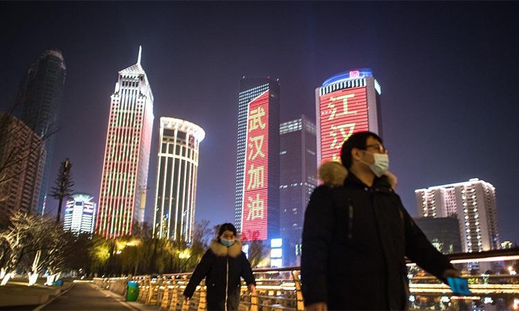 Các tòa nhà ở Vũ Hán, thủ phủ tỉnh Hồ Bắc, Trung Quốc chiếu các khẩu hiệu cổ vũ người dân giữa dịch Covid-19. Ảnh: Xinhua.