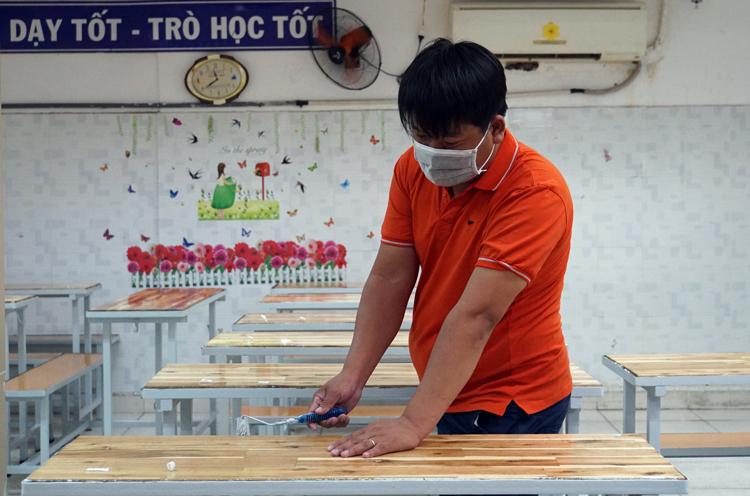 Nhân viên trường THCS - THPT Hồng Hà sơn lại bàn ghế học sinh. Ảnh: Mạnh Tùng.