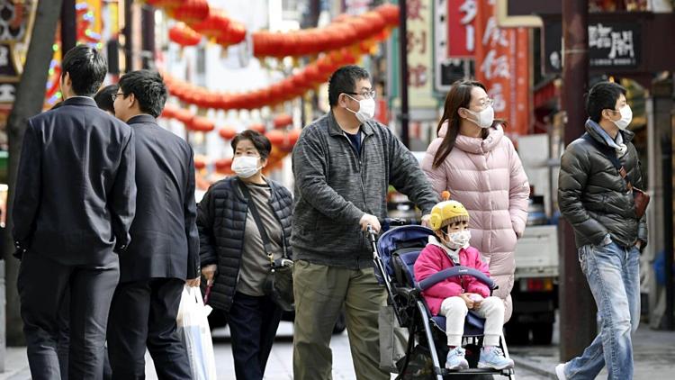 Người dân Nhật Bản sử dụng khẩu trang khi ra đường. Ảnh: Kyodo News