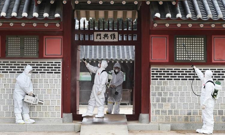 Các quan chức y tế tẩy trùng một ngôi điện cổ ở Suwon ngày 30/1. Ảnh: Reuters.