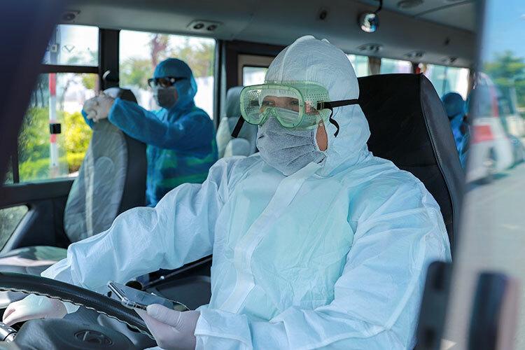 Lái xe, nhân viên y tế đều được trang bị đồ bảo hộ. Ảnh: Nguyễn Đông.