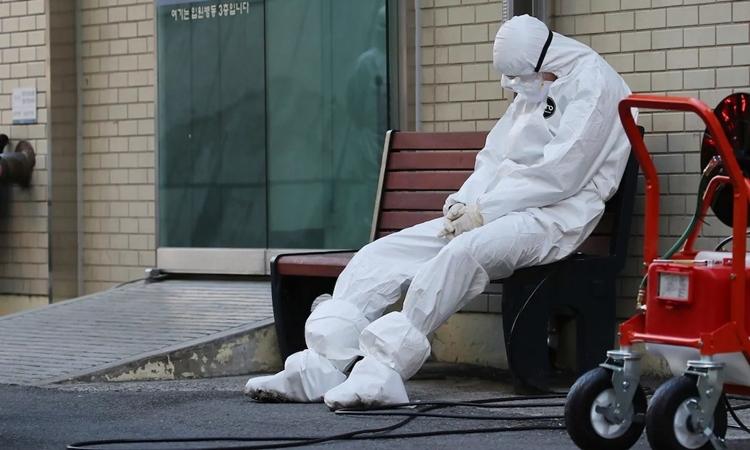 Nhân viên y tế nghỉ ngơi tại lối vào một bệnh viện ở Daegu ngày 23/2. Ảnh: AFP.