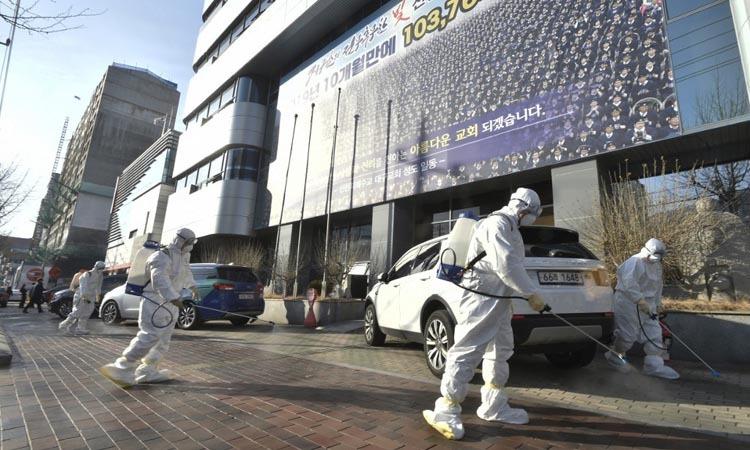 Các nhân viên y tế khử trùng trước nhà thờ Tân Thiên Địa ở Daegu, Hàn Quốc hôm 19/2. Ảnh: AFP.