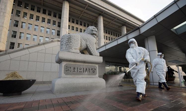 Nhân viên kiểm dịch phun khử trùng tại tòa nhà quốc hội Hàn Quốc ở Seoul hôm 24/2. Ảnh: AFP.