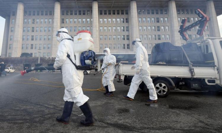 Nhân viên y tế phun khử trùng tại tòa nhà quốc hội Hàn Quốchôm 24/2. Ảnh: AFP.