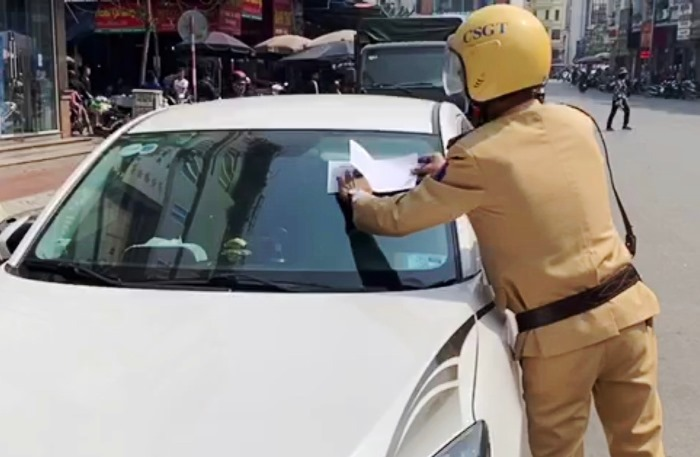 Cảnh sát giao thông dán thông báo lên xe vi phạm. Ảnh: M.C