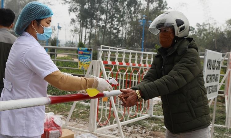 Nhân viên y tế xịt khử trùng cho người dân ở xãSơn Lôi, huyện Bình Xuyên, tỉnh Vĩnh Phúc hôm 20/2. Ảnh: Ngọc Thành.