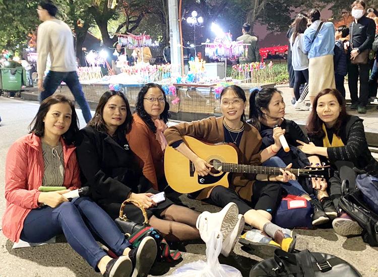 Cô Thu Bình (cầm đàn) cùng phụ huynh đàn hát trên phố đi bộ sau buổi họp sơ kết học kỳ I. Ảnh: Nhân vật cung cấp.