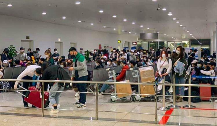 Hành khách từ Hàn Quốc về Việt Nam tối 27/2 ngồi chờ để kiểm soát y tế. Ảnh:Giang Kim Bùi
