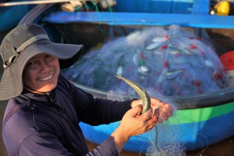 Anh Nguyễn Văn Hoàng, ngư dân Phan Thiết đang gỡ cá mòi ra khỏi lưới. Ảnh: Việt Quốc