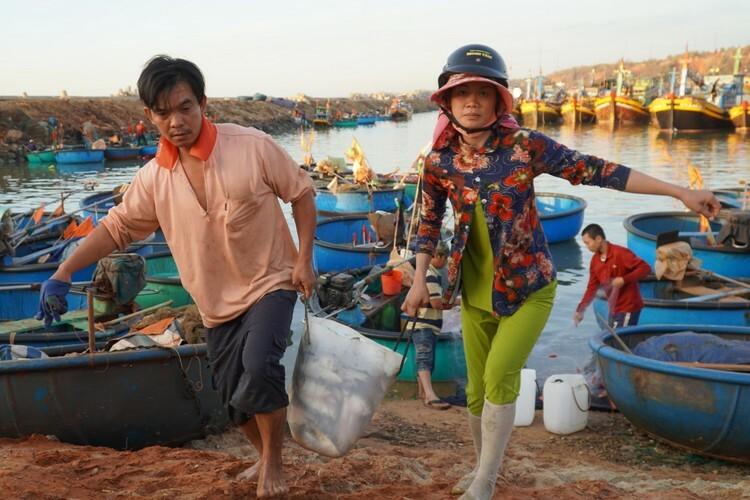 Cá đầy thùng, ngư dân khiêng lên bờbán ngay cho thương lái để kịp buổi chợ. Ảnh: Việt Quốc