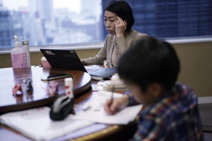 Kobayashi đưa con trai đến nơi làm việc sáng 2/3. Ảnh: AP Photo/Eugene Hoshiko