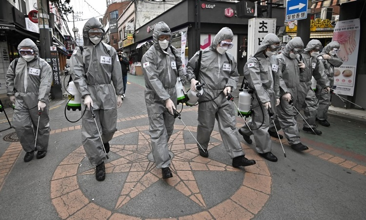 Binh sĩ Hàn Quốc mặc đồ bảo hộ phun thuốc khử trùng tại một quận mua sắm ở thủ đô Seoul hôm nay. Ảnh: AFP.