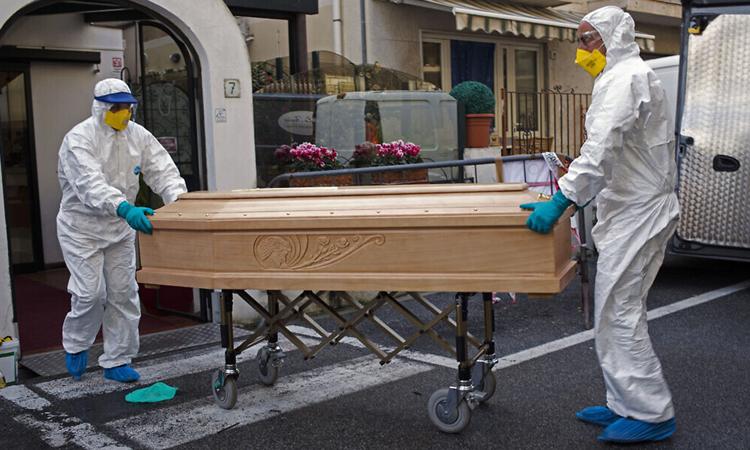 Nhân viên y tế chuyển quan tài của cụ bà 87 tuổi qua đời vì nhiễm nCoV ở Laigueglia, vùng Liguria hôm 1/3. Ảnh: AP.