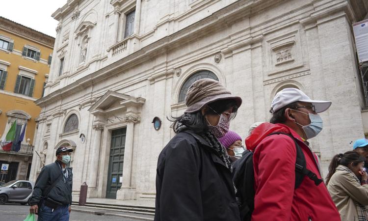 Hai du khách (phải) đeo khẩu trang đứng bên ngoài nhà thờ St. Louis ở Rome hôm 1/3. Ảnh: AP.