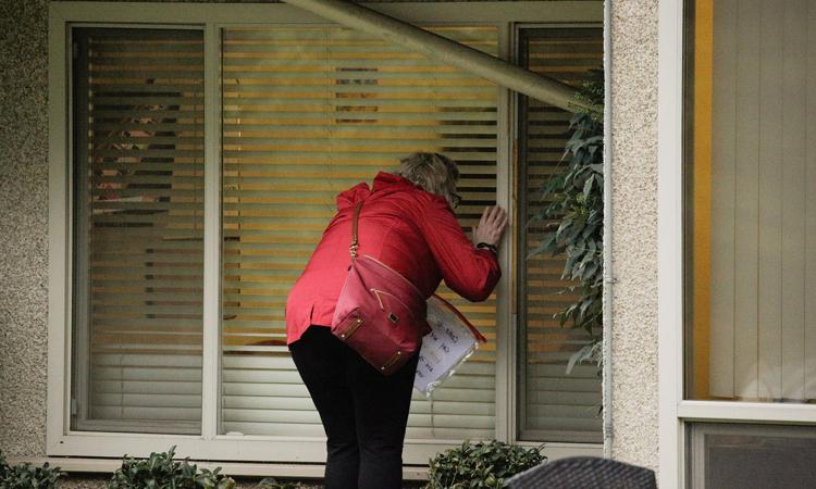 Người phụ nữ đứng nhìn mẹ qua cửa sổ ở viện dưỡng lão  Life Care Center ở thành phố Kirkland. Ảnh: Reuters.