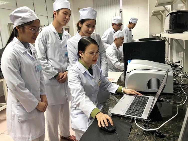 TS Hằng hướng dẫn các học viên quan sát biểu đồ nCoV trên máy real-time RT-PCR. Ảnh: BN