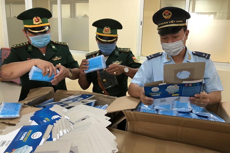 Lực lượng chức năng kiểm tra số khẩu trang không có giấy tờ liên quan. Ảnh: An Phú