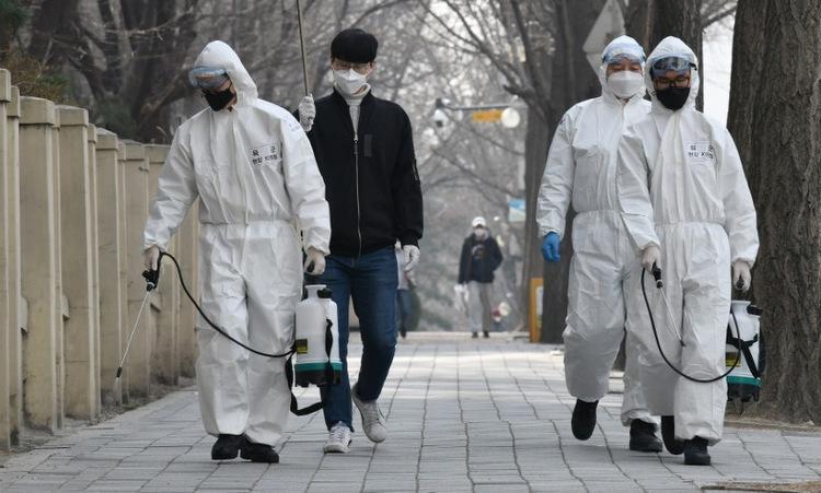 Binh sĩ Hàn Quốc phun khử khuẩn trên đường phố Seoul hôm 9/3. Ảnh: AFP.