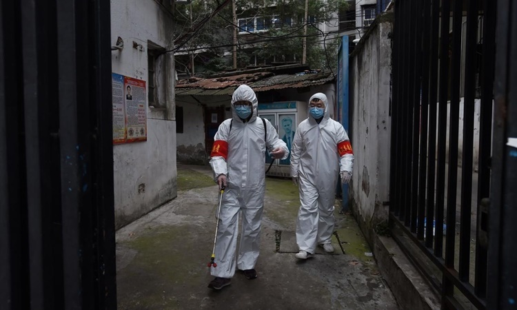 Nhân viên y tế tẩy trùng một khu dân cư ở Vũ Hán ngày 6/3. Ảnh: Reuters.