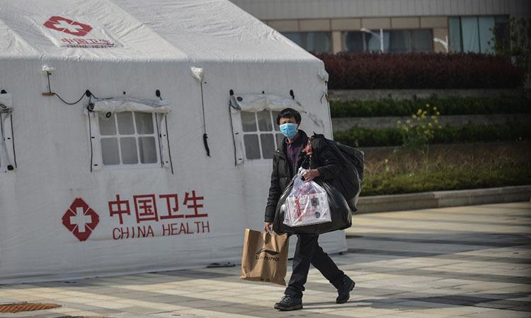 Một bệnh nhân Covid-19 bình phục rời bệnh viện dã chiến ở Vũ Hán, tỉnh Hồ Bắc, Trung Quốc hôm nay. Ảnh: AFP.
