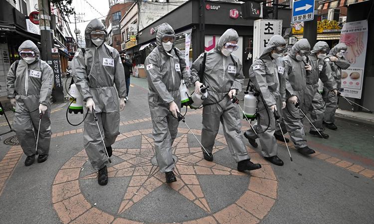 Binh sĩ Hàn Quốc mặc đồ bảo hộ đi phun hóa chất khử trùng ngăn Covid-19 tại thủ đô Seoul ngày 4/3. Ảnh: AFP.