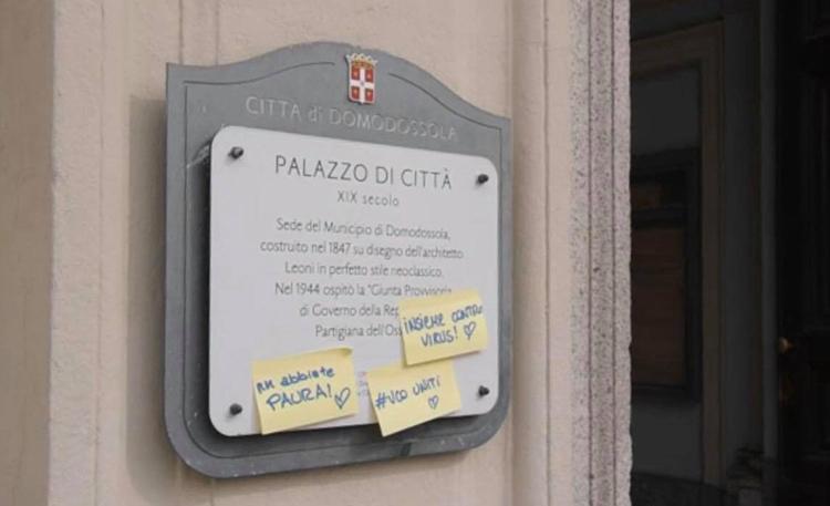 Những thông điệp kêu gọi đoàn kết và động viên người dân được dán ở bảng hiệu của tòa thị chính thành phố Domodossola hôm 10/3. Ảnh: Stella Vũ