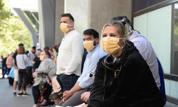 Izzy (phải) ngồi chờ xét nghiệm nCoV bên ngoài Bệnh viện Hoàng gia Melbourne hôm 10/3. Ảnh: Herald Sun.