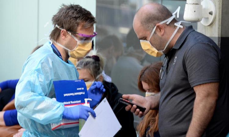 Nhân viên y tế nói chuyện với người đứng chờ xét nghiệm bên ngoài Bệnh viện Hoàng gia Melbourne hôm 10/3. Ảnh: Herald Sun.