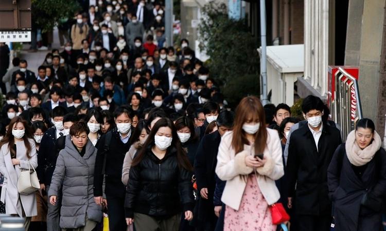 Người dân Tokyo, Nhật Bản ra đường trong giờ cao điểm hôm 20/2. Ảnh: AP.