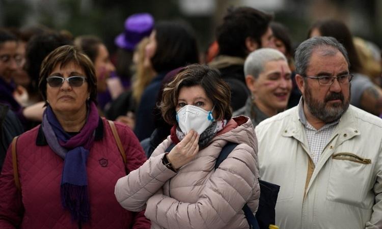 Một phụ nữ đeo khẩu trang giữa những người không có dụng cụ bảo hộ nào tại sự kiện kỷ niệm Ngày Quốc tế Phụ nữ 8/3 ở Madrid, Tây Ban Nha. Ảnh: AFP.