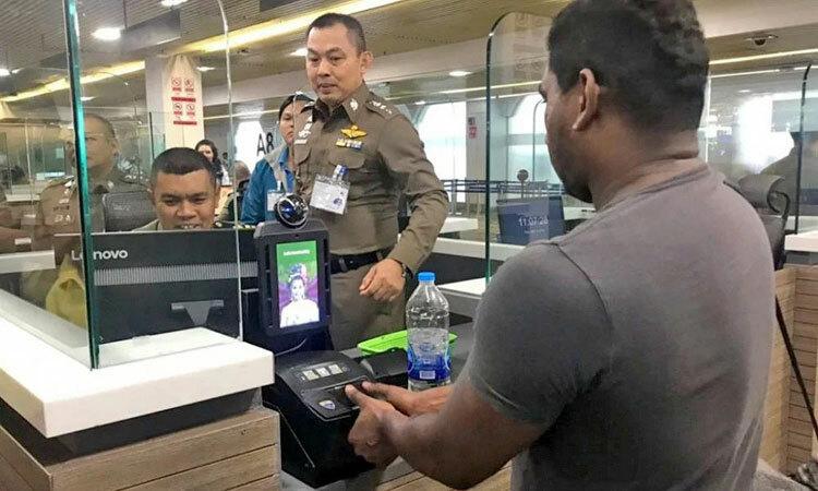 Nhân viên kiểm soát xuất nhập cảnh Thái Lan hướng dẫn hành khách lấy vân tay. Ảnh: Thaiger.