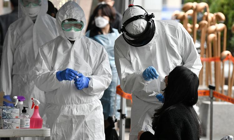 Nhân viên y tế Hàn Quốc ngày 10/3 lấy mấu xét nghiệm cho người lao động tại một tòa nhà ở Seoul, nơi phát hiện 46 ca nhiễm nCoV. Ảnh: AFP.