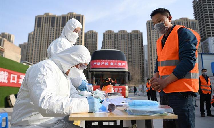 Công nhân đăng ký trước khi vào làm việc tại một công trường ở thành phố Lan Châu, tỉnh Cam Túc, Trung Quốc ngày 3/3. Ảnh: Xinhua.