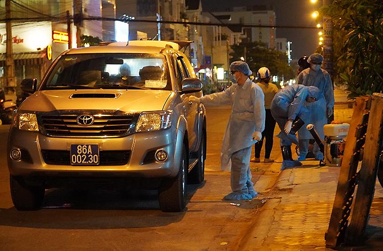 Nhân viên y tế chuẩn bị phun thuốc khử trùng khu vực nhà bệnh nhân 34 ở thành phố Phan Thiết, tối 10/3. Ảnh: Việt Quốc.