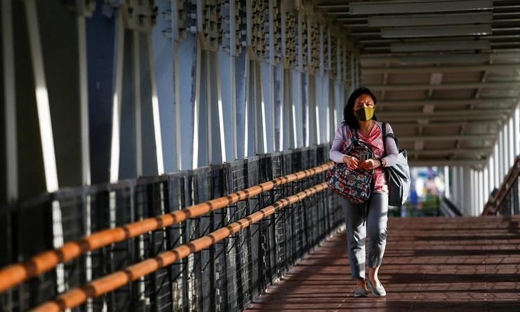 Người phụ nữ đeo khẩu trang bảo hộ đi trên một cây cầu ở thủ đô Jakarta, Indonesia hôm 9/3. Ảnh: Reuters.