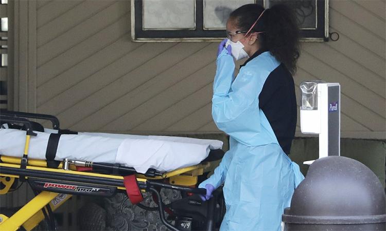 Nhân viên y tế Mỹ lấy cáng ra khỏi xe cứu thương tại viện dưỡng lão Life Care, Kirkland, bang Washington ngày 5/3. Ảnh: Reuters.