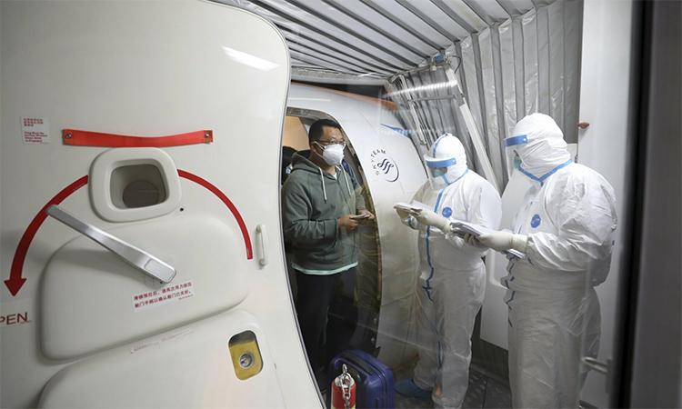 Công dân tỉnh Hồ Bắc được nhân viên y tế kiểm tra sau khi hạ cánh tại Vũ Hán ngày 31/1. Ảnh: AFP.