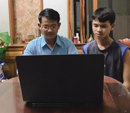 Anh Đặng Hùng Phi cùng con trai ôn bài qua các video bài giảng.