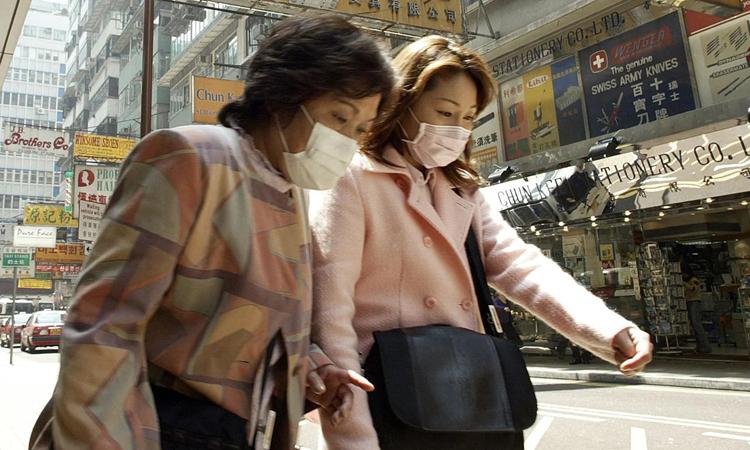 Hai người phụ nữ đeo khẩu trang ở Hong Kong ngày 25/3/2003 khi dịch SARS bùng phát. Ảnh: AFP.