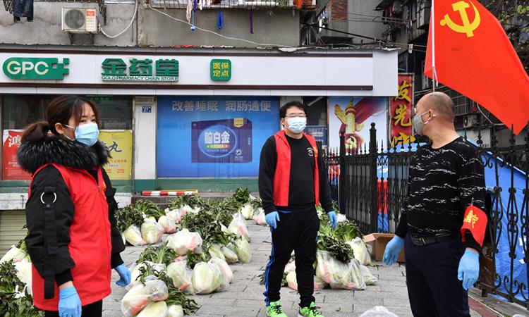 Tình nguyện viên đeo khẩu trang chuẩn bị phân phát rau tại một khu dân cư ở Hồ Bắc, Trung Quốc hôm 5/3. Ảnh: Reuters.