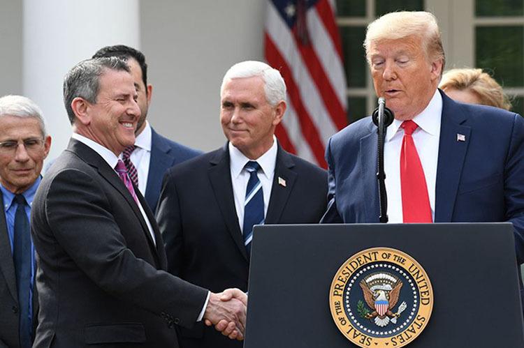 Tổng thống Mỹ Donald Trump (phải) bắt tay Chủ tịch Tập đoàn bán lẻ Target Brian Cornell tại buổi họp báo ở Nhà Trắng hôm 13/3. Ảnh: AFP.