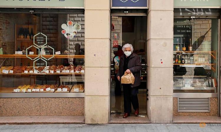 Một phụ nữ đeo khẩu trang tại một cửa hàng ở Barcelona, Tây Ban Nha hôm 13/3. Ảnh: Reuters.