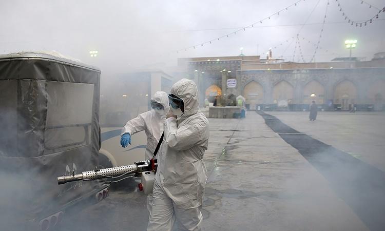 Nhân viên y tế khử trùng một ngôi đền ở Mashhad, Iran, ngày 27/2. Ảnh: Reuters.