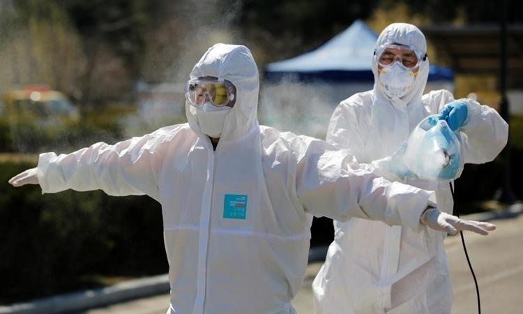 Nhân viên kiểm dịch phun khử trùng nhân viên phản ứng khẩn cấp ở Daegu ngày 14/3. Ảnh: Reuters.