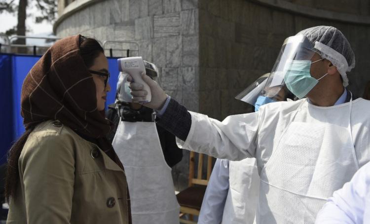 Nhân viên y tế đo thân nhiệt một người dân tại trung tâm Kabul hôm 9/3. Ảnh: AFP.