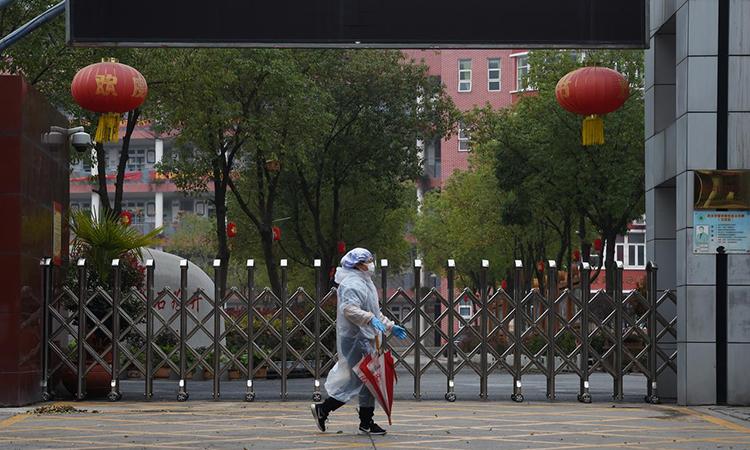 Người dân mặc áo mưa, đeo khẩu trang đi qua cổng một trường trung học ở Vũ Hán, thủ phủ tỉnh Hồ Bắc, Trung Quốc hôm 9/3. Ảnh: Reuters.