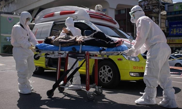 Nhân viên y tế đưa người nghi nhiễm nCoV tới bệnh viện ở Daegu hôm 12/3. Ảnh: AFP.
