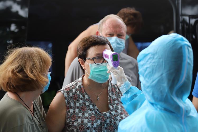 Nhân viên y tế đo thân nhiệt cho khách đến Đà Nẵng bằng đường bộ, tại chốt chân đèo Hải Vân sáng 16/3. Ảnh: Nguyễn Đông.