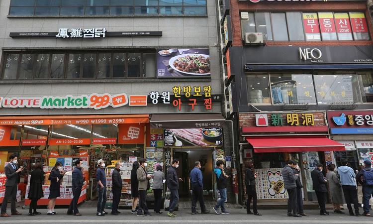 Người dân xếp hàng mua khẩu trang bên ngoài một hiệu thuốc ở Seoul hôm 12/3. Ảnh: AP.